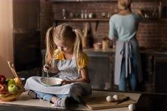 Яичка включенной девушки смешивая сидя на таблице Стоковое Изображение RF