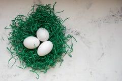 Яичка в зеленой книге гнездятся 3 белых яичка Стоковые Фотографии RF