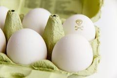 Яичка в пакете зеленой книги с одним из яичек покрашенных с ядовитым черепом и косточками символа риска Стоковое Изображение RF