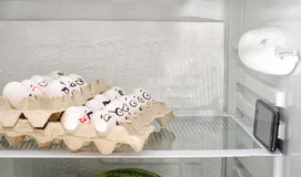 Яичка в подносах на полке холодильника, расположенной как в кинотеатре Покрашенные стороны смотря телефон Стоковые Изображения