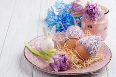 Яичка в связанных шляпах, цветках и декоративном кролике Стоковое Изображение RF