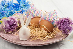 Яичка в связанных шляпах, цветках и декоративном кролике Стоковые Изображения