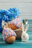 Яичка в связанных шляпах, цветках и декоративном кролике Стоковое Изображение