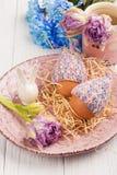 Яичка в связанных шляпах, цветках и декоративном кролике Стоковое фото RF