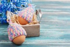 Яичка в связанных шляпах, цветках Стоковая Фотография