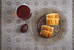 Яичка горячих перекрестных плюшек, чашки чаю и шоколада на таблице пасхи Стоковая Фотография