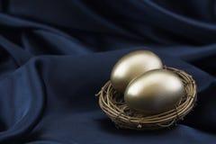 2 яичка золота в гнезде на черной предпосылке сатинировки Стоковые Изображения RF