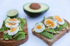 Яичка и авокадо на провозглашанном тост хлебе Стоковое фото RF