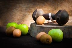 Яичка, киви, измеряя тип, яблоко и гантели для тренировки Стоковое Изображение