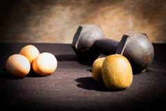 Яичка, киви и гантели для тренировки Стоковые Изображения RF