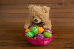 Яичка пасхи красочные в корзине и плюше носят Стоковое Изображение