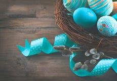 Яичка пасхи красочные покрашенные с цветками весны и голубой лентой сатинировки Стоковое Изображение