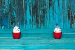 Яичка с улыбкой в красных стойках, голубой предпосылкой, концепцией пасхи Стоковые Изображения