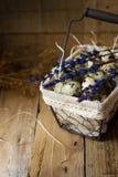 Яичка триперсток в выровнянной корзине провода, на соломе, с хворостинами лаванды, пасха, деревенский интерьер стоковые изображения