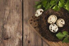Яичка триперсток в гнезде на деревянной предпосылке Стоковая Фотография RF