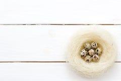 Яичка триперсток пасхи в гнезде на белой деревянной предпосылке Стоковая Фотография