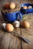 Яичка фермы в голубых чашке и ложке Стоковые Фотографии RF