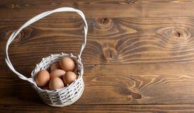 Яичка цыпленка в белой корзине на деревянном столе 2 всех пасхального яйца принципиальной схемы цыпленока ведра цветут детеныши п Стоковая Фотография RF