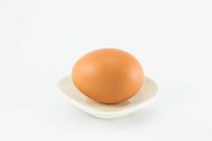 Яичко на белом блюде Стоковые Изображения