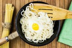Яичница и спагетти в черном лотке на деревянном столе стоковые фотографии rf