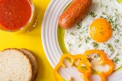 Яичница с сосиской и отрезанным желтым перцем на плите рядом с стеклом сока томата и кусками хлеба на желтой предпосылке Стоковое Фото