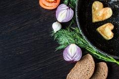 Яичницы в форме сердца в сковороде, около которой куски хлеба положения, красный лук, томат, чеснок и укроп Стоковое Изображение RF