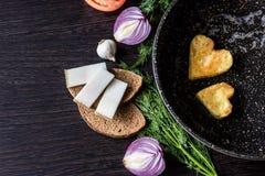 Яичницы в форме сердца в сковороде, около которой куски хлеба положения, salo шпика, красный лук, томат, чеснок и укроп Стоковое Фото