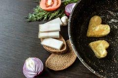 Яичницы в форме сердца в сковороде, около которой куски хлеба положения, salo шпика, красный лук, томат, чеснок и укроп Стоковые Изображения