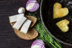 Яичницы в форме сердца в сковороде, около которой куски хлеба положения, salo шпика, красный лук, томат, чеснок и укроп Стоковые Изображения RF