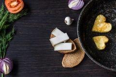 Яичницы в форме сердца в сковороде, около которой куски хлеба положения, salo шпика, красный лук, томат, чеснок и укроп Стоковая Фотография RF