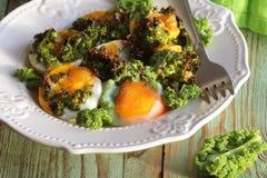 Яичницы с листьями зеленого цвета листовой капусты на завтрак стоковые фото