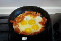 Яичницы с томатом в сковороде Взбитые яйца и томат на сковороде стоковые фотографии rf