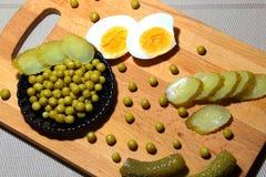 Яичный желток, замаринованные корнишоны и законсервированные зеленые горохи для варить шум стоковая фотография rf