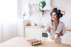 Яйца красивой жизнерадостной славной молодой домохозяйки смешивая в кухне Смотреть, который нужно встать на сторону и усмехнуться стоковое изображение rf