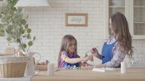 Яйца маленькой девочки крася с ее матерью используя небольшую щетку Счастливая семья Подготовка пасхи сток-видео