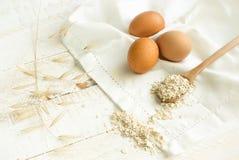 Яйца свободного ряда органические коричневые разлили овсы на деревянной ложке на белом деревянном столе полотенца хлопка Сбаланси стоковые изображения