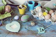 Яйца, триперстки, оформление пасхи на голубом деревянном столе стоковая фотография