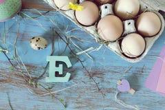 Яйца, триперстки, оформление пасхи на голубом деревянном столе стоковая фотография rf