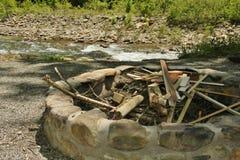 Яма пожара около реки заполненного с древесиной Стоковые Изображения