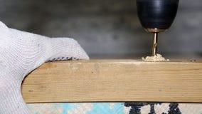 Яма сверла прорезывает в деревянный блок, делая отверстие акции видеоматериалы