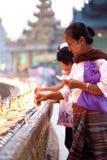 ЯНГОН, МЬЯНМА - 29-ОЕ ЯНВАРЯ: Женщина буддиста освещает ручки амулета на виске 29-ое января 2010 Shwedagon, Мьянме Стоковое фото RF