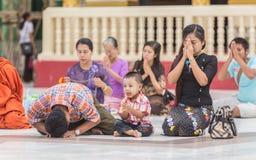 ЯНГОН, МЬЯНМА - UNE 22, 2015: Люди Мьянмы молят к Будде i Стоковое Изображение
