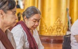 ЯНГОН, МЬЯНМА - UNE 22, 2015: Люди Мьянмы молят к Будде i Стоковые Фото