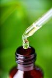 янтарная жидкость падения бутылки стоковое изображение