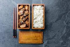 Японская еда Teriyaki цыпленка с рисом в деревянной коробке для завтрака бенто Предпосылка шифера, взгляд сверху стоковые фотографии rf
