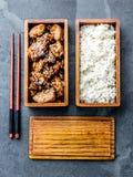 Японская еда Teriyaki цыпленка с рисом в деревянной коробке для завтрака бенто Предпосылка шифера, взгляд сверху стоковая фотография rf