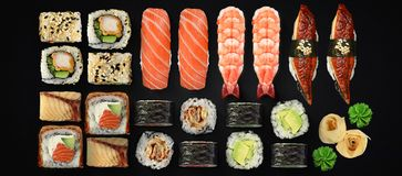 Японская кухня Суши и крены установленные над темной предпосылкой Стоковые Изображения