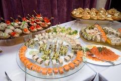 Японская кухня - суши стиля ресторанного обслуживании шведского стола установите в ресторан - salmon суши Maki и суши Nigiri Селе Стоковое Изображение RF