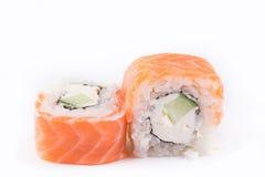 Японская кухня, установленные суши: семги свертывают с сыром и огурцом на белой предпосылке Стоковое фото RF