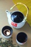 Японская церемония чая, белый бак чая фарфора с бамбуковой ручкой и иероглифы с 2 чашками чая, зеленый чай разбросали и выкрикива Стоковое Изображение RF